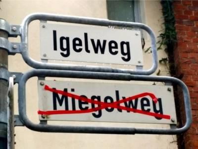 Auf dem Bild sind zwei Straßen Schilder zu sehen. Auf dem oberen Schild steht Igelweg, auf dem unteren Schild steht Miegelweg rot durchgestrichen.