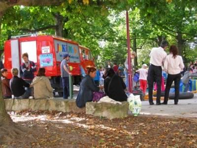 Eltern schauen den Kindern beim spielen beim Kinderfest zu. Daneben steht ein JuKiMob Feuerwehrauto.