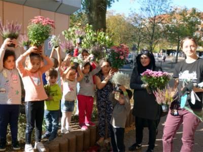 Anja Krause (1.v.r.) und Hanan Fakih (2.v.r.) von den Internationalen StadtteilGärten mit Kindern aus der Gärtnergruppe Steigerwaldweg pflegen eines der größten Beete im Einkaufszentrum Hägewiesen.