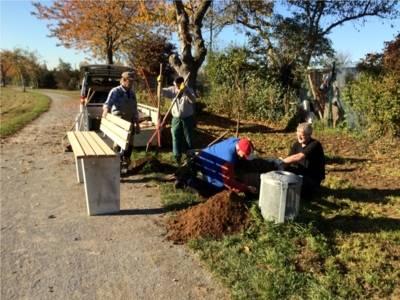 Vier Arbeiter montieren die neuen Bänke am Mittellandkanal. Die Bänke müssen dafür in die Erde eingelassen.