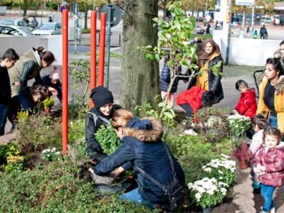 Hanan Fakih (Mitte links) bepflanzt gemeinsam mit Müttern und Kindern der Internationalen StadtteilGärten ein Hochbeet im Einkaufszentrum Hägewiesen.