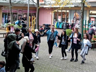 """Insa Prätsch (Mitte), Pädagogische Leiterin des NaDu-Kinderhaues, tanzt gemeinsam mit Kindern der NaDu-Tanzgruppe und Bewohnern beim Herbstfest """"Sahlkamp blüht"""" im Einkaufszentrum Hägewiesen."""