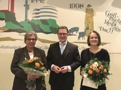 Gruppenfoto: Rechts und links des Bezirksbürgermeisters Henning Hofmann die beiden geehrten Frauen, die eine Urkunde und einen Blumenstrauß in Händen halten.