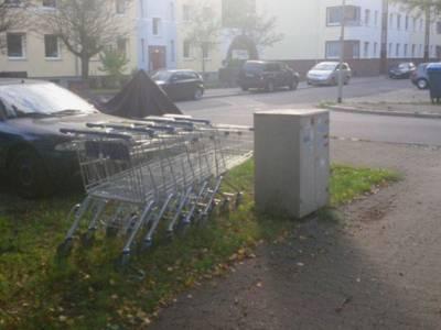 Mehrere ineinandergeschobene Einkaufswagen stehen im Wohngebiet herum.