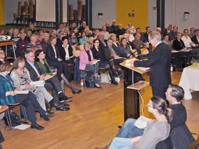 Am Rednerpult steht Oberbürgermeister Schostok und berichtet über die Entwicklungen und Planungen im Stadtbezirk Buchholz-Kleefeld.