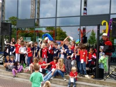Eine große Gruppe von Kinder führt etwas vor. Die Kinder stehen zum größten Teil zusammen. Einige Kinder sitzen davor einige singen am Mikrofon.