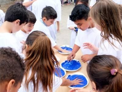 Auf dem Bild sind mehrere Kinder zu sehen, die ihre Hände in Malfarben tauchen. Die Malfarbe ist blau.