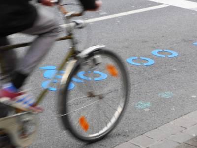 Ein Radfahrer fährt an den Symbolen des City-Radrings vorbei