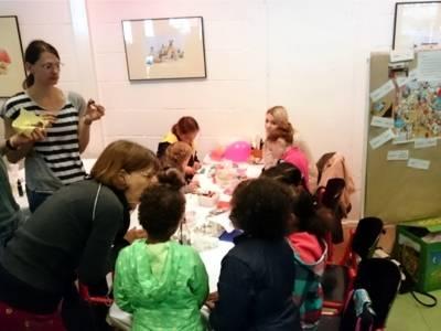 Eine Gruppe von Kindern bastelt zusammen an einem Tisch. Erwachsene beaufsichtigen die Kinder dabei.