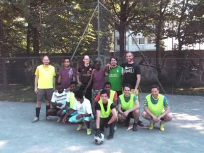 Mehrere Männer stehen auf einem Bolzplatz und machen ein Mannschaftsfoto. Vor der Mannschaft liegt ein Fußball.