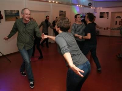 Mehrere Tanzpaare tanzen zusammen auf der Tanzfläche.