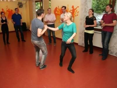 Ein Tanzpaar tanzt auf der Tanzfläche. Drei Tanzpaare schauen dem Tanzpaar beim tanzen zu.