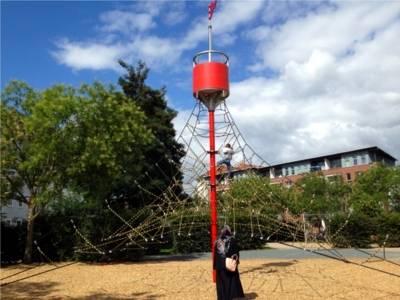 Auf dem Bild ist ein Klettergerüst auf einem Spielplatz zu sehen an dem ein Kind klettert. Eine Mutter steht dabei.
