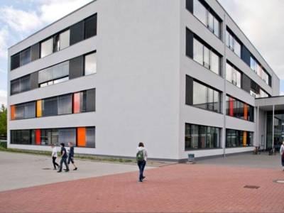 Auf dem Bild ist das moderne Gebäude der IGS Mühlenberg zu sehen. Ein paar Schüler sind vor der Schule zusehen.