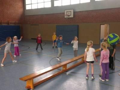 Kinder spielen in einer Turnhalle mit einem großen Ball.