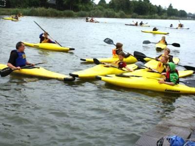 Kinder in Kanus auf einem Gewässer.