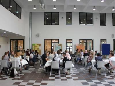 Menschen an Tischen in einer Halle.