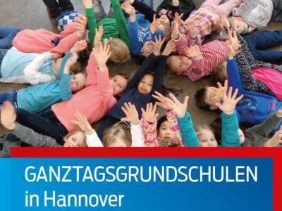Kinder liegen im Kreis auf dem Boden und strecken ihre Arme dem Betrachter entgegen