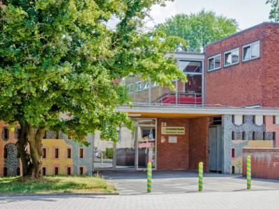 Der Eingang zur Grundschule Beuthener Straße führt in ein zweistöckiges Backsteingebäude mit Glaselementen im 1. Stock. Rechts und links ist die Fassade mit bunten Mosaiksteinen verziert