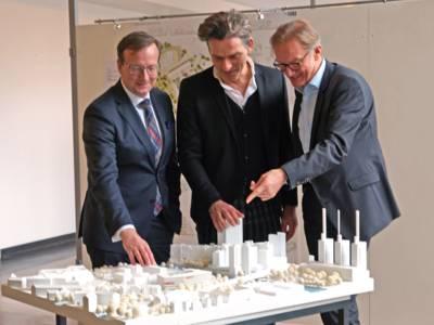 Drei Männer, die auf ein Architekturmodell zeigen.