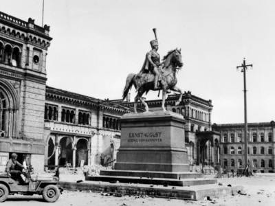 Jeep vor einem Denkmal auf einem leeren Platz im Jahr 1945.
