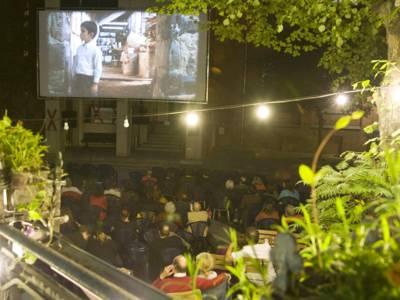 Menschen vor einer Open Air Kino-Leinwand