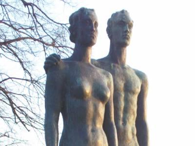 Die Doppelskulptur zeigt eine Frau und einen Mann ohne Bekleidung, die nebeneinander stehen.