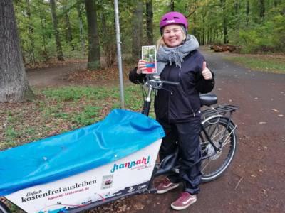 """Junge Frau mit wetterfester Kleidung steht mit einem Lastenfahrrad auf einem Fahrradweg durch ein Waldstück und hält den Flyer """"Julius-Trip-Ring"""" und einen Daumen in die Höhe."""