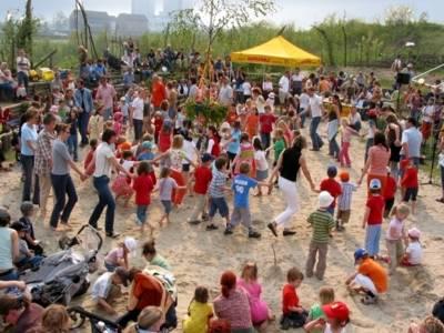 Zahlreiche Kinder und Erwachsene halten sich an den Händen und tanzen auf Sand um einen Maibaum herum