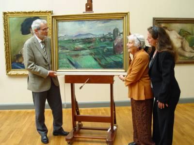 In einem Museumsraum stehen neben einem ausgestellten Gemälde, das eine italienische Landschaft zeigt, drei Personen: links der ehemalige Kulturdezernent Böhlmann, rechts davon eine ältere Dame und eine Frau mittleren Alters.