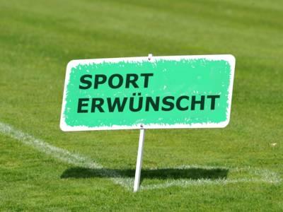 """Rasenfläche, auf der ein Schild steht, auf dem """"Sport erwünscht"""" zu lesen ist."""