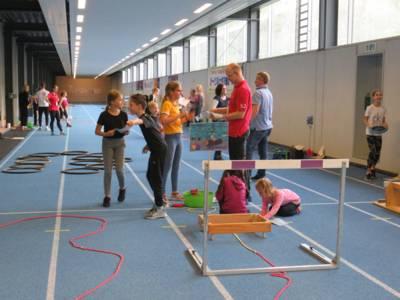 Kinder und Jugendliche an Sportständen in einer Halle.
