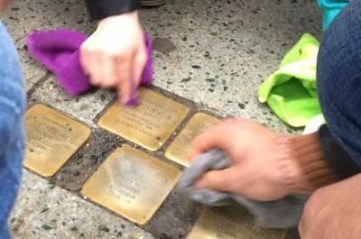 Schüler und Schülerinnen polieren die Stolpersteine in der Langen Laube 1 auf Hochglanz.