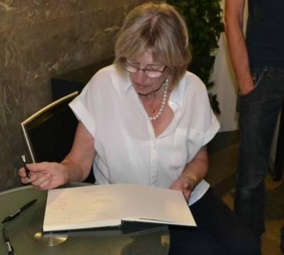 """Christa Brebeck, die Cousine von Robert Salau, trägt sich in das Besucherbuch im Gedenkraum """"Grotte"""", Neues Rathaus, ein."""