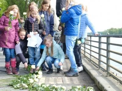 Schüler*innen der Tellkampfschule legen Rosen am Gedenkstein für die Bücherverbrennung 1933 nieder.