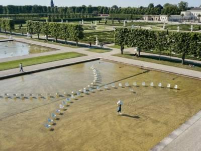 Eine Frau in einem Teich, die Stühle hin- und herstellt.