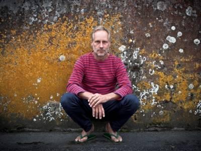 Wolfram Koch hockt vor einer bemoosten Wand