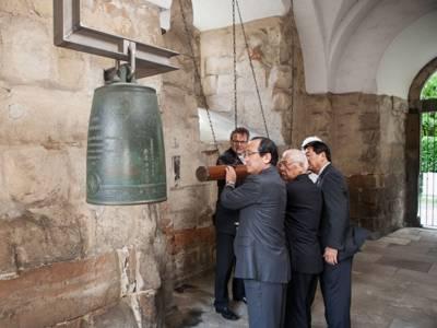 Männer, die eine Glocke anschlagen.