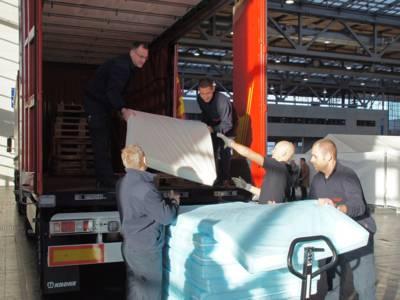 Fünf Feuerwehrleute entladen Matratzen aus einem LKW