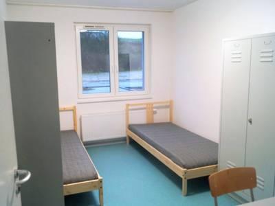 Blick in ein Zimmer im Flüchtlingswohnheim Hermann-Ehlers-Allee: Zwei Betten, zwei Spinde, ein Tisch und zwei Stühle