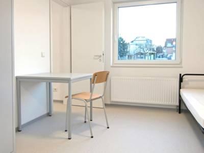 Ein Zimmer mit Bett, Schrank, Tisch und Stuhl.