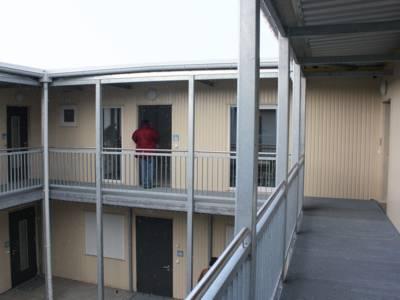 Die Wohnungen im Obergeschoss sind über einen vorgestellten Laubengang erschlossen, der gleichzeitig als Rettungsweg dient