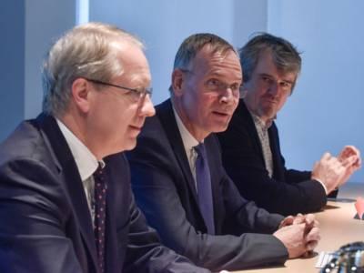 Drei Männer an einem Tisch.