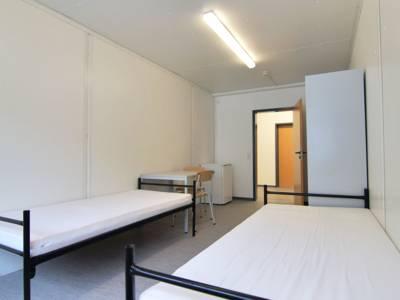 Zwei Betten, ein Tisch, zwei Stühle, die Seite eines Spindes und ein Kühlschrank in einem Zimmer der Flüchtlingsunterkunft Waterlooplatz