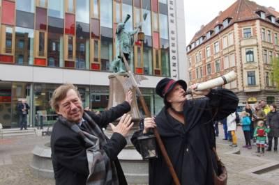 Zwei Männer vor einem Brunnen.