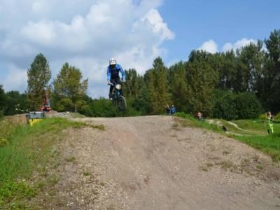 BMX-Fahrer im Sprung über einen Hügel.