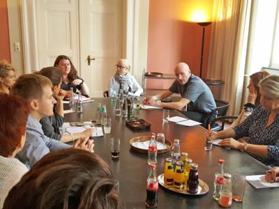 Eine Gruppe Menschen sitzt zur Besprechung um einen Tisch.