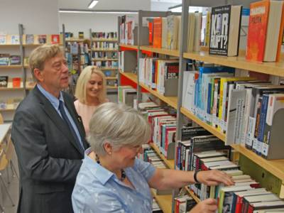 Ein Mann und zwei Frauen vor einem Bücherregal.