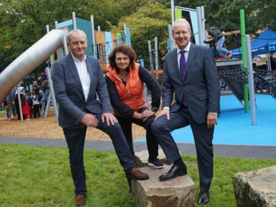 Zwei Männer und eine Frau auf einem Spielplatz.