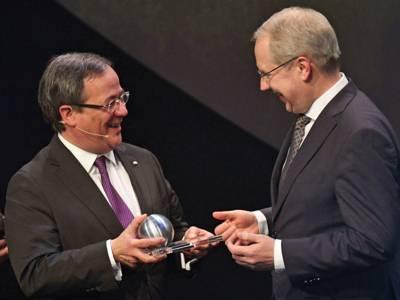 Der Ministerpräsident von Nordrhein-Westfalen, Armin Laschet, überreicht dem Oberbürgermeister von Hannover, Stefan Schostok, einen Preis in Form einer Kugel.